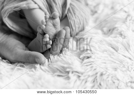 Newborn baby  legs under the openwork blanket openwork