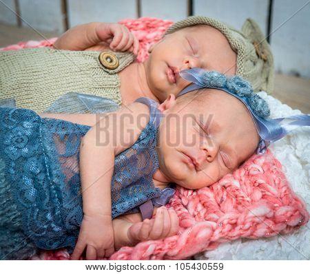 newborn twins - a boy and a girl sleeping in a basket closeup