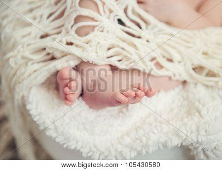 Newborn baby  legs under the openwork blanket openwork