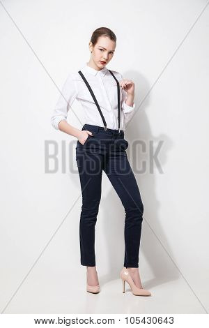 fashion model in black trousers and top posing over white