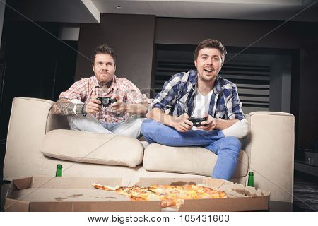 Two young men playing video games while sitting on sofa