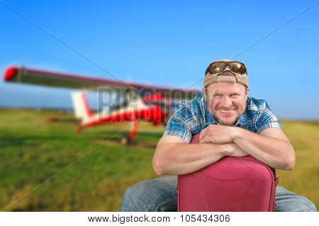 Tourist man sitting with suitcase at air field