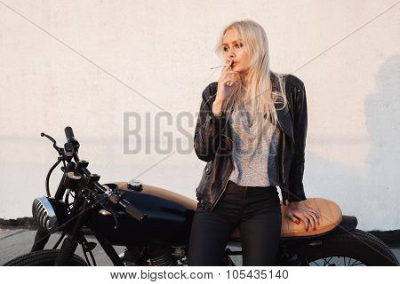 Woman Sitting On Vintage Motorcycle And Smoking Sigarette