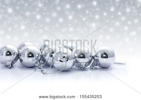 Silver christmas balls on snow background