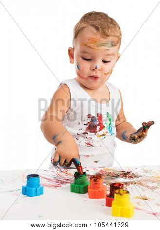 funny little boy painting with hands paper and himself on a white background