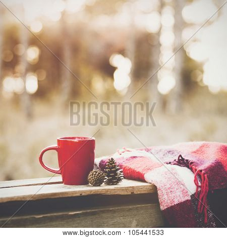 Cup of tea and warm plaid blanket on wooden rustic bench in the autumn forest. Fall weekend. Photo toned, selective focus.