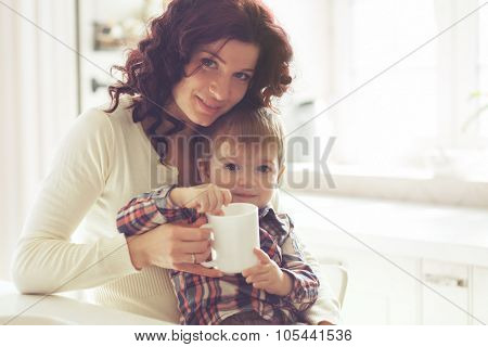 Mother with her baby having breakfast in the bright kitchen at home. Photo toned, still life.