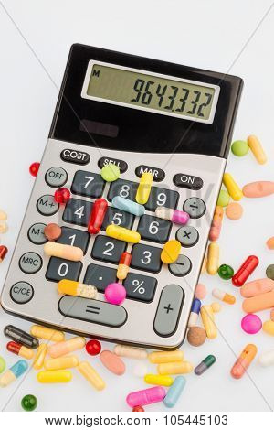 tablets lie on a calculator. symbol photo for costs in medicine and pharmaceutical industry