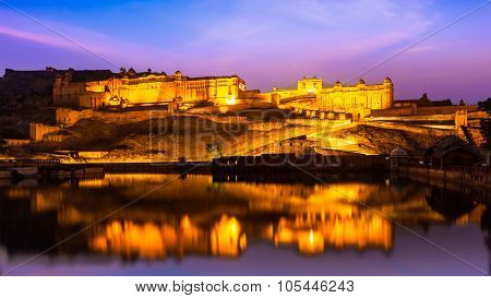 Panorama of Amer Fort (Amber Fort) illuminated at night - one of principal attractions in Jaipur, Rajastan, India refelcting in Maota lake in twilight