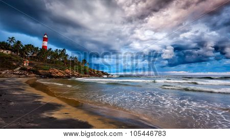 Panorama of gathering storm on beach and Kovalam (Vizhinjam) lighthouse on stormy sunset. Kerala, India