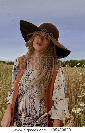 Beautiful Girl Sitting In A Wheat Field