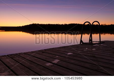 Night swim dock and calm lake at twilight