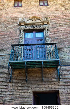 BARCELONA, SPAIN - MAY 02: Low Angle View of Balcony with Ornate Railing and Doorway on Exterior of Brick Building Wall, Barcelona, Spain. May 02, 2015