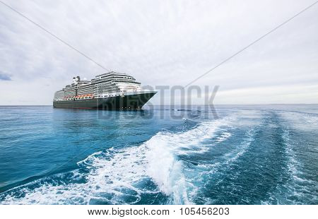 Cruise ship on a blue sea in the Bahamas under cloudy skies.