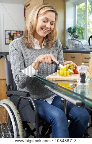 Disabled Woman In Wheelchair Preparing Meal In Kitchen