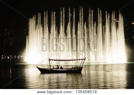 DUBAI, UAE - OCTOBER 15, 2014: The Dubai Fountain at night. The Dubai Fountain is the world's largest choreographed fountain system set on the 30-acre manmade Burj Khalifa Lake.