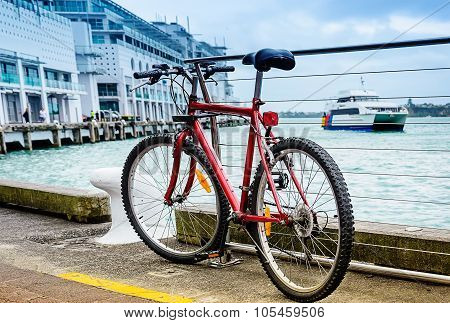 Red parked bicycle on the pier at harbor