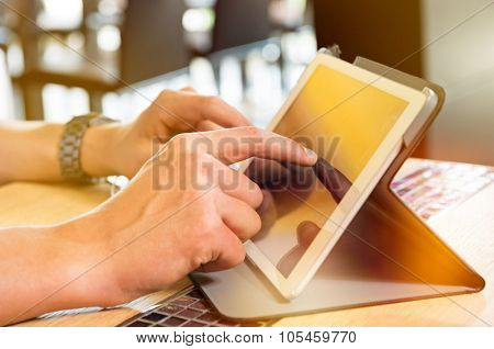 Closeup shot of man using digitaltablet. Guy is touching screen of tablet at cafe. Detail of a young man's hand typing on digital tablet at restaurant.