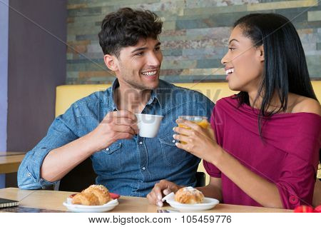 Closeup shot of couple looking at eachother and smiling at cafe. Multiethnic couple having breakfast with a cup of coffee. Happy young couple having fun during breakfast with brioches.