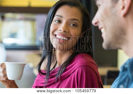 Closeup shot of young woman drinking a cup of coffee at caf�©. Young couple having breakfast at coffee bar. African young woman smiling at her boyfriend while drinking an espresso.