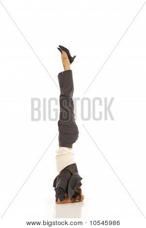 Young businesswoman in suit doing yoga Headstand Pose
