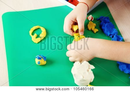 Cute little girl moulds from plasticine on table, close-up