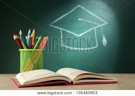 Metal cap of crayons with open book and bachelor hat drawing on blackboard background