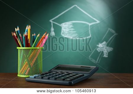 Metal cap of crayons with calculator and bachelor hat drawing on blackboard background