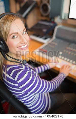 Portrait of happy young radio host working in studio
