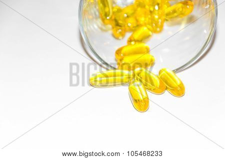 fish oil - omega 3 - yellow softgel capsules in a glass, white background