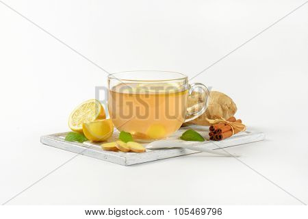 cup of ginger tea with lemon, fresh ginger and cinnamon on wooden cutting board