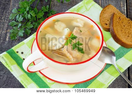 Soup With Fresh Fish And Dumplings On A Wooden Table