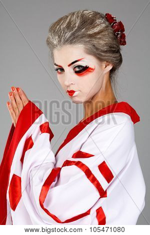 girl in traditional Japanese costume and makeup standing with hands clasped studio shot