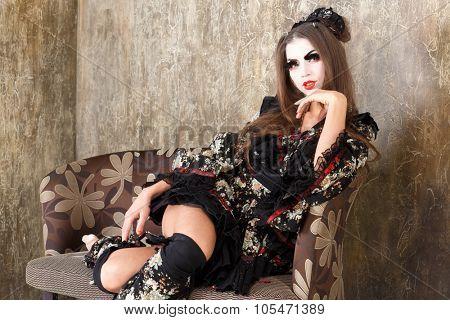 girl in kimono and traditional Japanise makeup sitting hand on chin studio shot