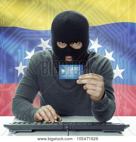 Dark-skinned Hacker With Flag On Background Holding Credit Card - Venezuela