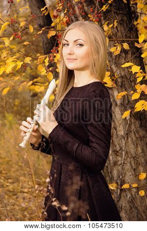 Beautiful Young Blonde Woman Posing With Flute Recorder In Autumn Forest
