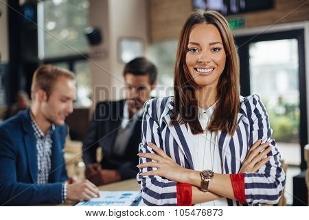 Young Businesswoman Posing In Front Of A Small Group Of Business People In Cafe