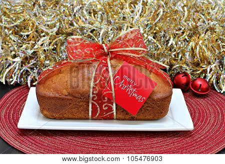 Pound Cake With A Christmas Ribbon And Merry Christmas Card.