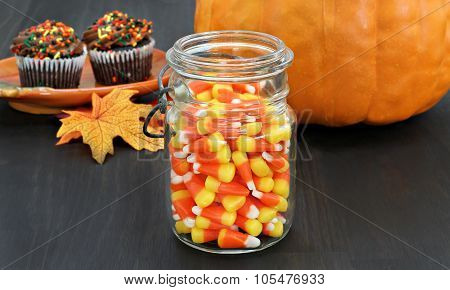 Candy Corn In A Rustic Mason Jar.  Pumpkin And Cupcakes In The Background.