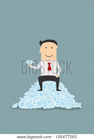 Businessman sitting on heap of shiny diamonds