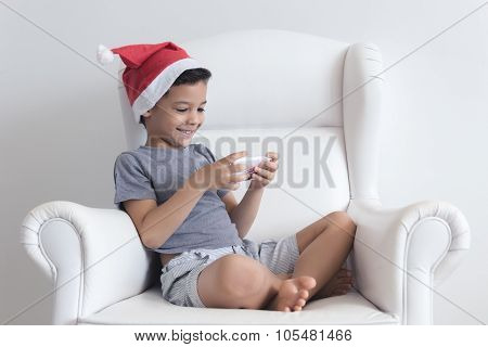Little Boy On The Sofa Playing On Mobile