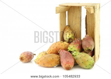 fresh colorful cactus fruit in a wooden crate on a white background