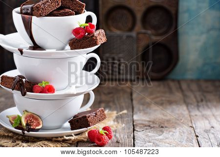 Brownies in stacked coffee cups with chocolate sauce