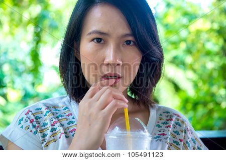 Asian Women Is Drinking Icetea At The Cafe