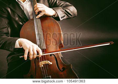 Man playing on cello on dark background