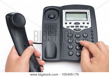 Man Dialing A Black Telephone On A White Background