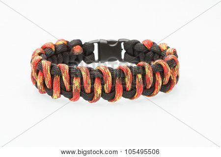 black and orange braided bracelet on white background