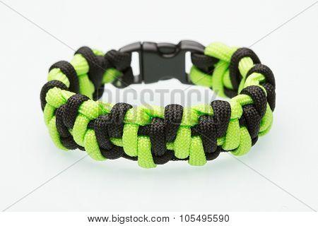 green braided bracelet on white background