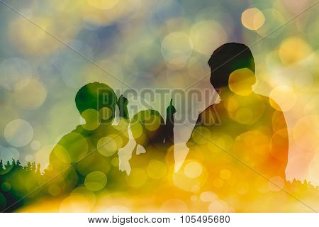 Silhouette Of Mother And Two Kids On Bokeh Abstract In Yellow Background