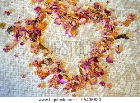 Heart of dried petals of tea rose on tablecloth with white roses and place for your text